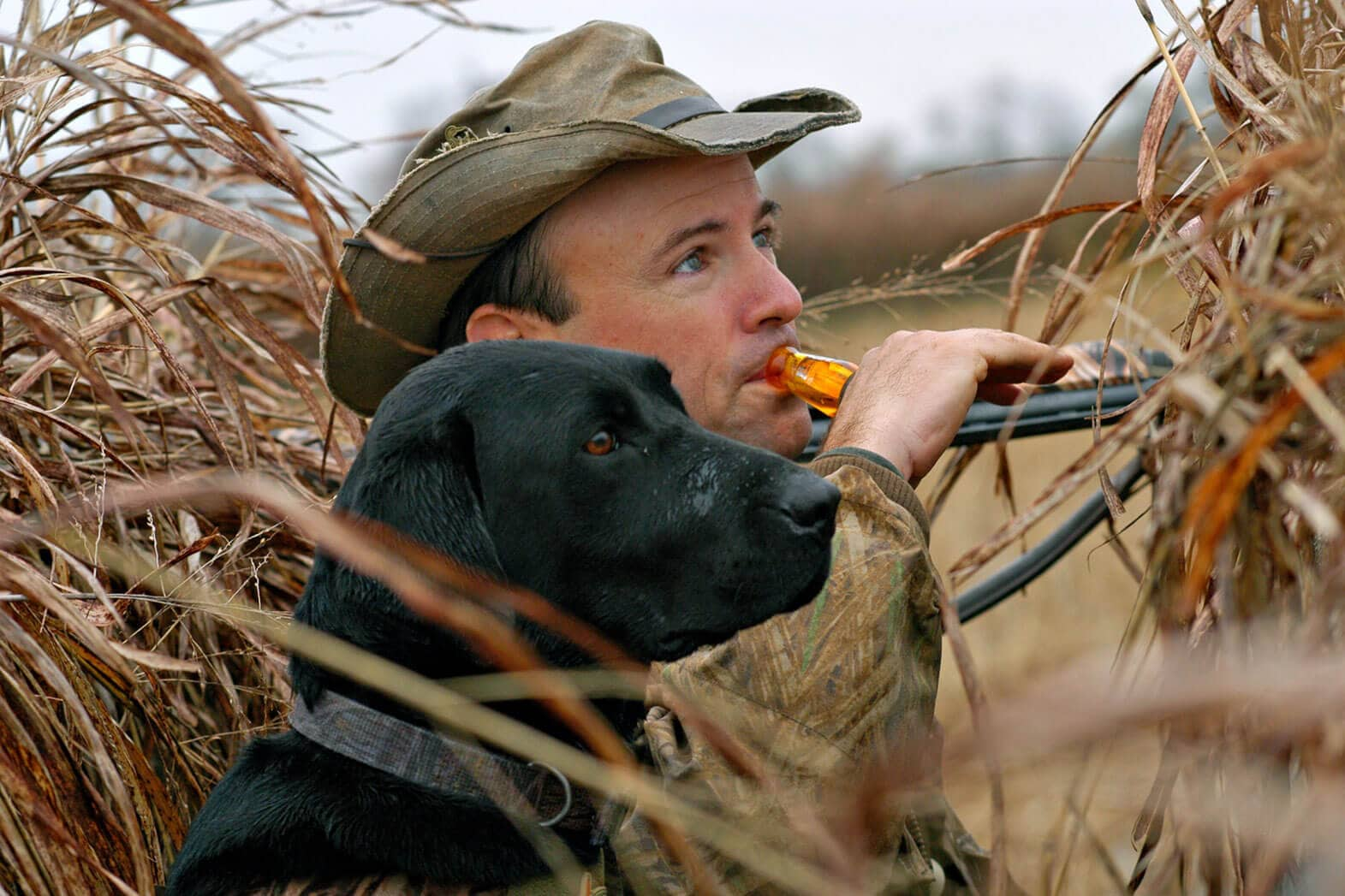 hunter using a duck call, and black dog